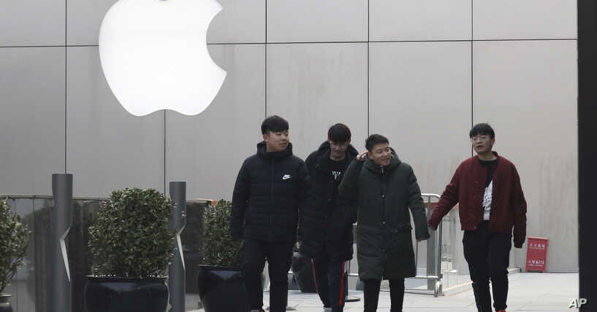 Chinese men walk past the Apple logo in Beijing, China, Thursday, Jan. 3, 2019. Apple Inc.'s $1,000 iPhone is a tough sell to Chinese consumers who are jittery over an economic slump and a trade war with Washington. The tech giant became the latest global company to collide with Chinese consumer anxiety when CEO Tim Cook said iPhone demand is waning, due mostly to China. Weak consumer demand in the world's second-largest economy is a blow to industries from autos to designer clothing that are counting on China to drive revenue growth. (AP Photo/Ng Han Guan)